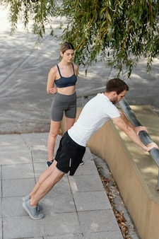 Woman and man exercising together outdoors