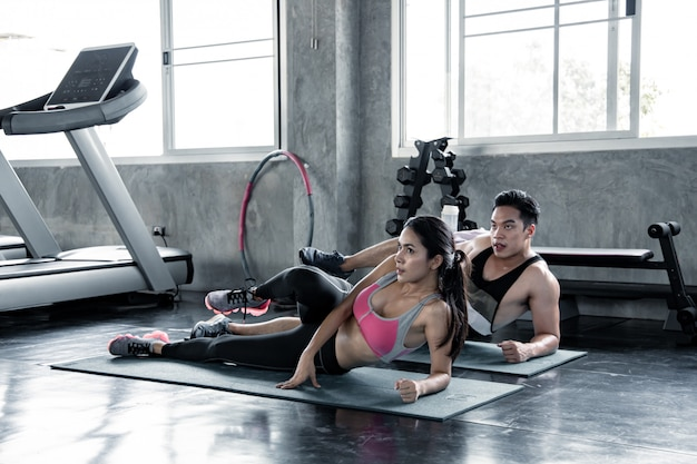 Woman and man exercising on yoga mat.
