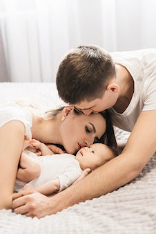 Woman and man holding a newborn. mom, dad and baby. close-up. portrait of young smiling family with newborn on the hands. happy family on a background.
