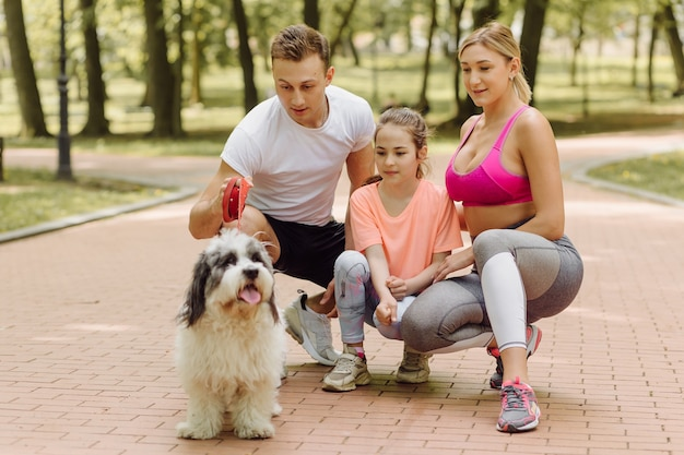 Woman, man and little girl go walking with their dog in the park