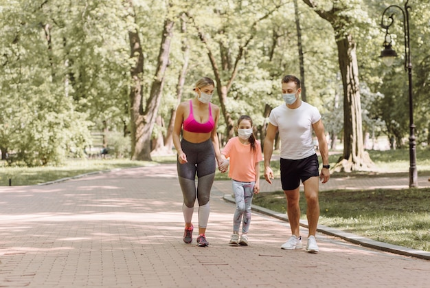 Woman, man and little girl jogging in the park