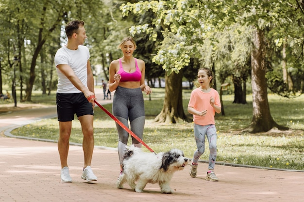 Woman, man and little girl jogging with their dog in the park
