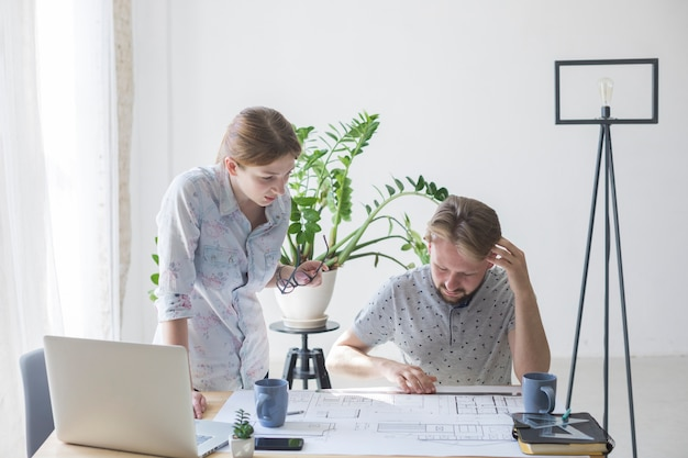 Woman and man looking at blueprint while working in office