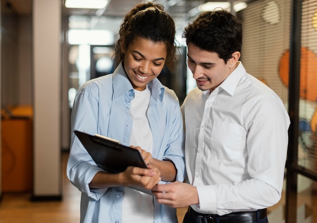 Woman and man looking at clipboard together at workplace