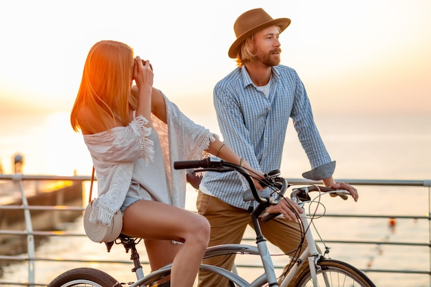 Woman and man in love traveling on bicycles at sunset sea