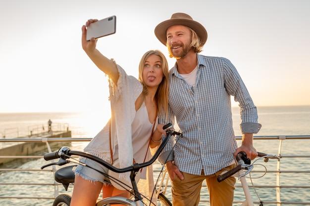 Donna e uomo innamorato che viaggiano in bicicletta al tramonto sul mare