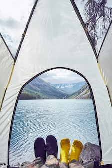 Woman and man lying in tent near lake with views