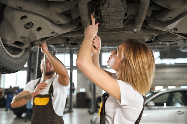 Woman and man mechanics repairing car undercarriage.
