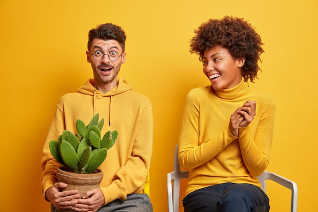 Woman and man move in new apartment pose on comfortable chairs on yellow