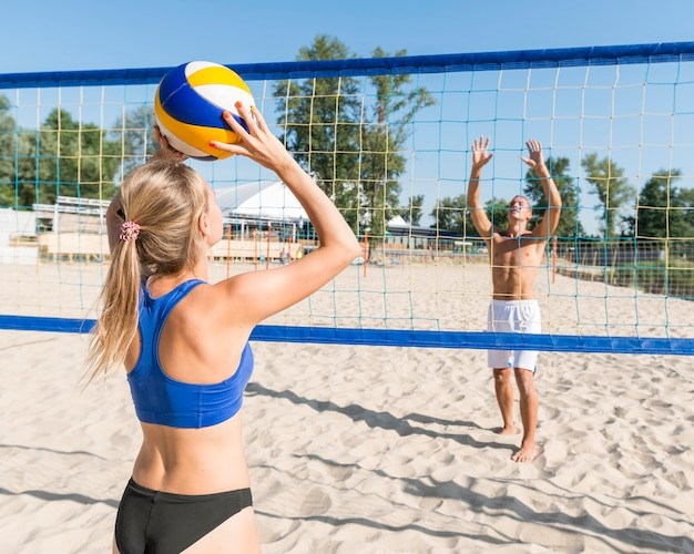Woman and man playing beach volleyball together