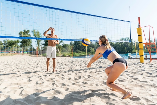 Woman and man playing beach volleyball