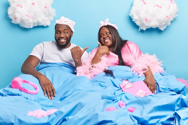 Woman and man point at each other enjoy spending time together pose under blanket in comfortable bed have day off isolated on blue