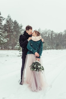 Woman and man portrait hugging together outdoors. winter fun outdoors. loving cute tender couple in love walking in showy forest together