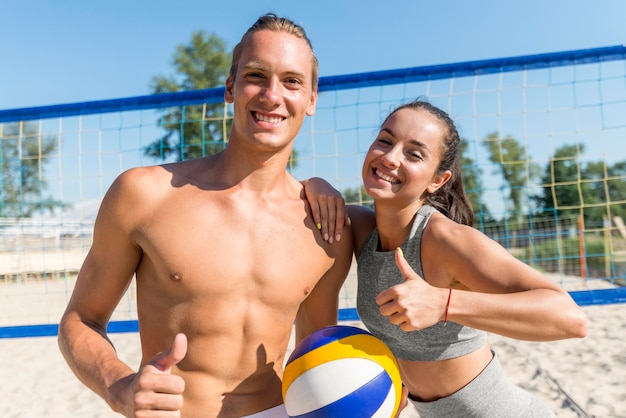 Woman and man posing with thumbs up while playing beach volleyball