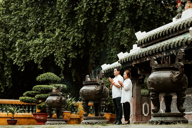 Woman and man praying at the temple with burning incense