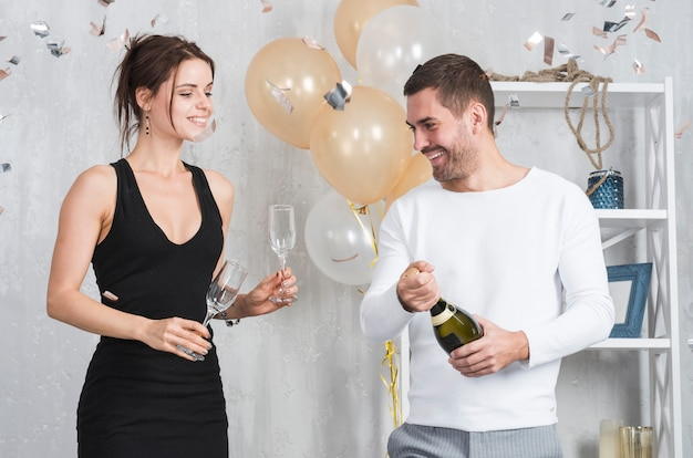 Woman and man preparing for drinking champagne
