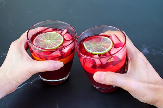 Woman and man's hand holding glass of red wine sangria on black table