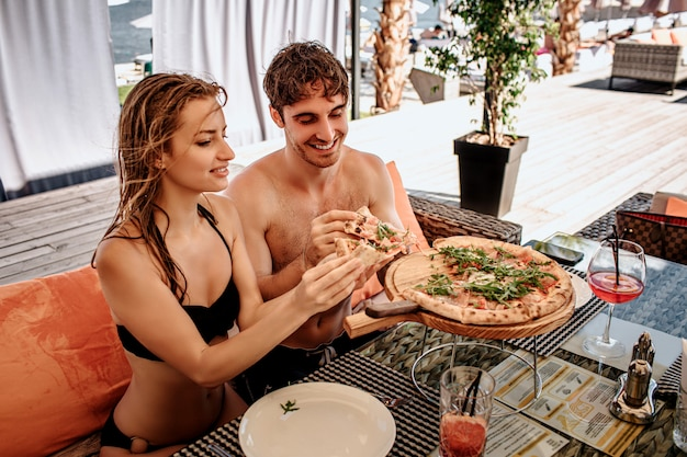 Woman and man sit in opened restaurant and eating tasty delicious pizza