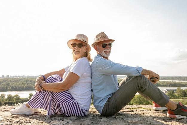 Donna e uomo seduto schiena contro schiena
