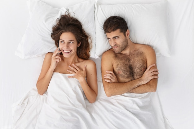 Woman and man sitting in bed top view