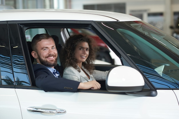 Woman and man sitting in car, looking at camera and smiling.