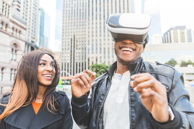 Woman and man smiling as he tries virtual reality headset