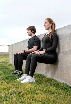 Woman and man in sportswear exercising outdoors