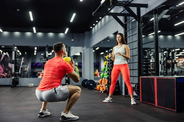 A woman and a man in sportswear throw a fitness ball in the gym. the man is in a squat position and is getting ready to throw the ball to the girl who is standing upright.sports challenge, couple goal