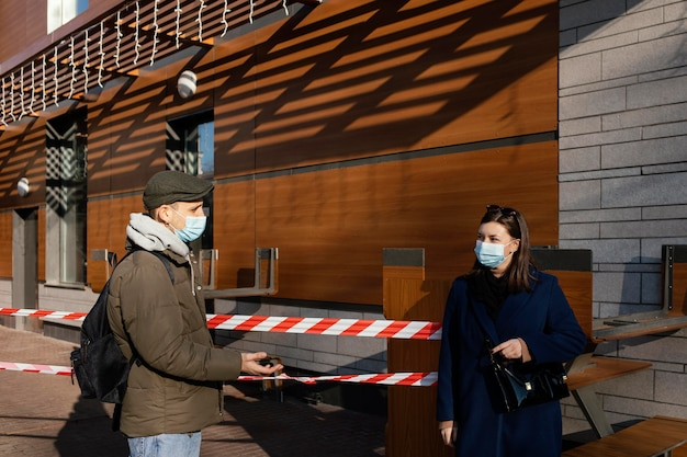 Woman and man on street wearing mask