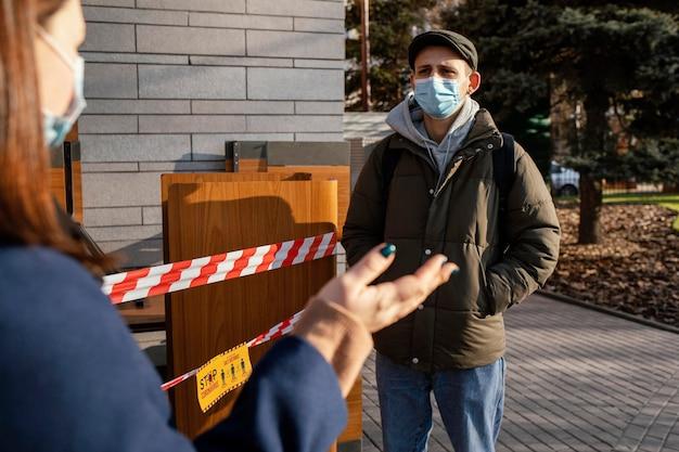 Donna e uomo sulla strada che indossa la maschera