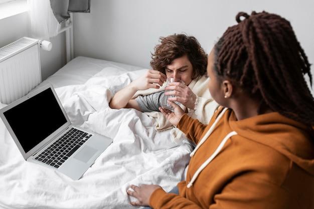 Donna e uomo che parlano con un medico tramite videochiamata