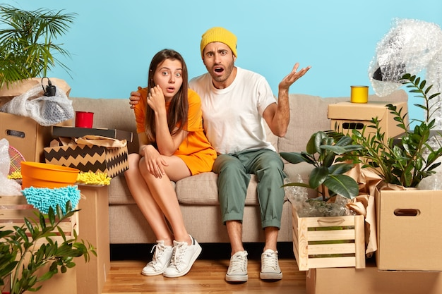 Woman and man tenants pose at cozy sofa in empty messy room with different household things, frustrated guy looks with great puzzlement, embraces girlfriend. couple moves in new flat for living