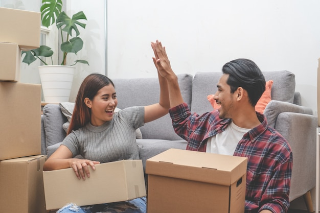 Woman and man unpacking messy boxes after moving in new house together.