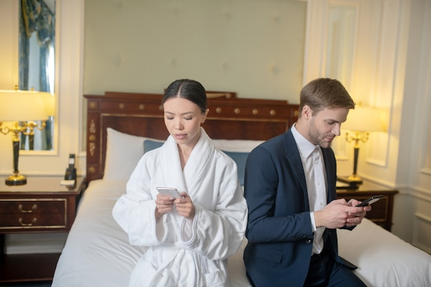 A woman and man using their smartphones in the bedroom
