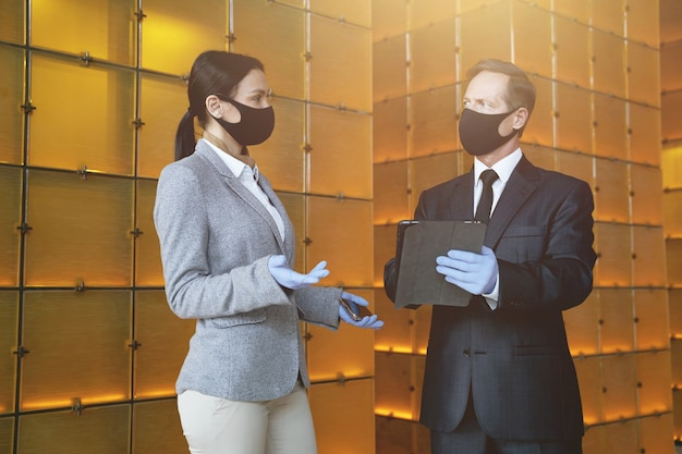 Woman and man wearing fabric masks and rubber gloves standing with modern devices and talking