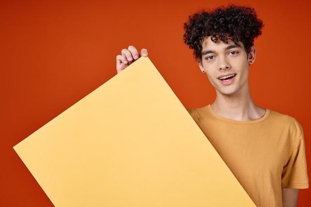 彼の手のスタジオのクローズアップでポスターを保持している巻き毛の女男