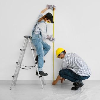 Donna e uomo con verniciatura di attrezzature di protezione di sicurezza