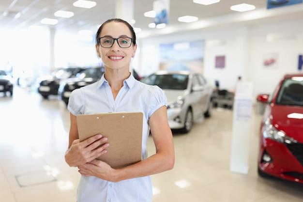 Женщина-менеджер-консультант стоит в автосалоне, покупая новую концепцию автомобилей