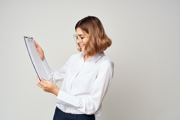 手ドキュメントオフィスにフォルダーを持つ白いシャツの女性マネージャー。高品質の写真