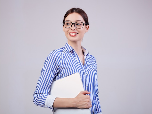 Woman manager in a striped white-blue shirt with glasses and a laptop on gray. employee of the year, business lady.