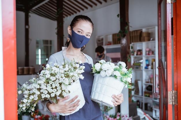 スタッフとバケツの花を持って立っているフェイスマスク花屋を身に着けている女性マネージャー