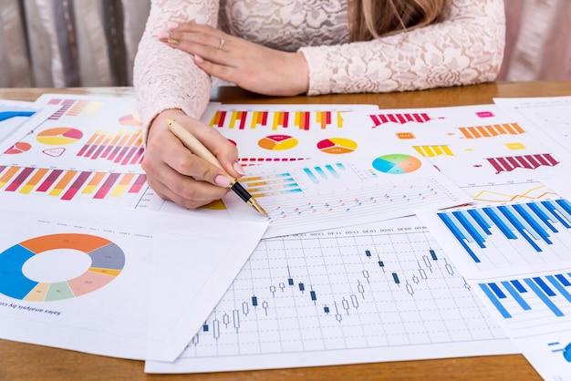 Женщина-менеджер, работающая с бизнес-графиками и диаграммами