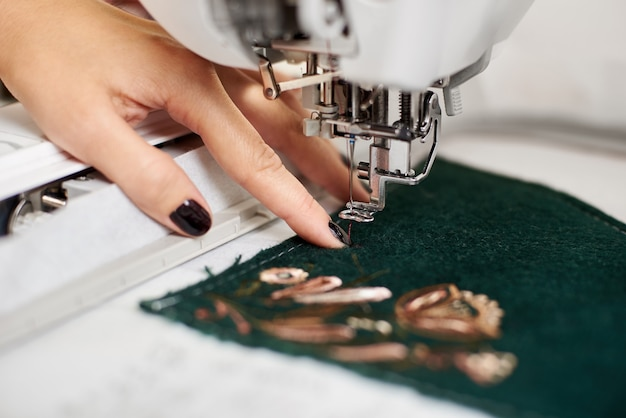 Woman manicured hand working on sewing machine