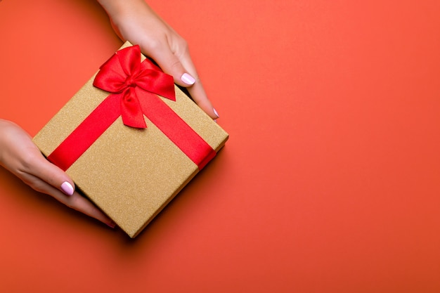 Woman manicured hands holding red and golden wrapped present or gift box
