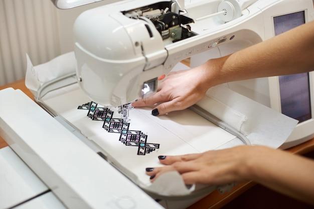 カラフルな幾何学模様を作成するミシンで働く女性の手入れの行き届いた手