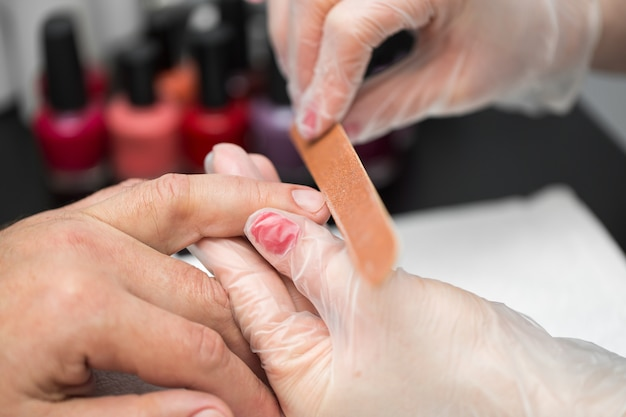 Woman manicurist doing manicure for man in beauty salon