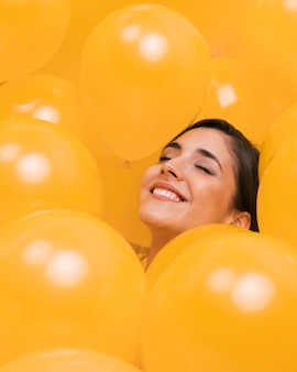 Woman between many yellow balloons