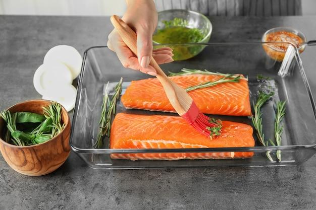 Женщина маринование филе лосося в форме для выпечки