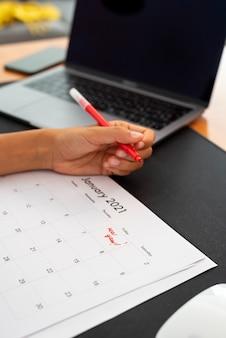 Woman marking january first on a calendar
