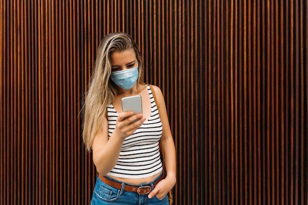 Woman in mask in the city using her mobile phone during the coronavirus pandemic